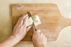 Men`s hands cutting raw dough Royalty Free Stock Images