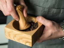 Men`s hands grind spices in a mortar. Men`s hands grind spices in a wooden mortar Royalty Free Stock Photography