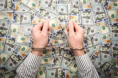 Men`s hands in handcuffs on background of dollar bills royalty free stock images