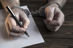 Men`s hands with handcuffs fill the police record, confession. On top see the police investigative detective. Arrest, bail, criminal, prison. Close-up Stock Photography