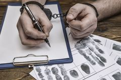Men`s hands with handcuffs fill the police record, confession. stock images