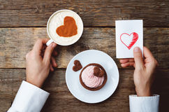 Men's hands hold cup of coffee and a greeting card for Valentine Stock Photo