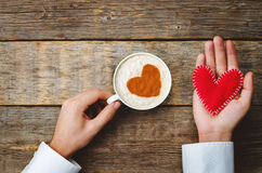Men's hands hold cup of coffee and a toy heart for Valentine's D Royalty Free Stock Photo