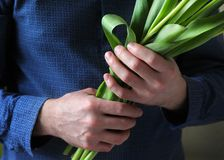 Men`s hands hold flowers. Man with flowers. Flowers for your beloved woman. A bouquet in hands. Date. Confession. Men`s hands hold flowers. Man with flowers Stock Photos