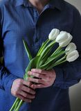 Men`s hands hold flowers. Man with flowers. Flowers for your beloved woman. A bouquet in hands. Date. Confession. stock photo