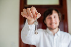Men`s hands hold house key on a background of a wooden door. Owning real estate concept Stock Photos