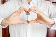 Men`s hands hold house key in the form of heart on the background of a wooden door. Owning real estate concept Royalty Free Stock Images