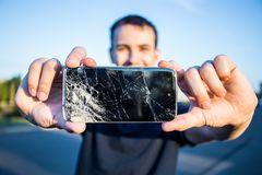 Smart phone with a cracked screen. Men`s hands hold a smart phone with a cracked screen royalty free stock photos