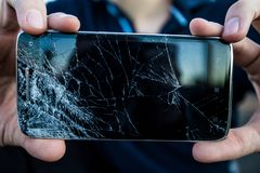 A smartphone with a cracked screen. Men`s hands hold a smartphone with a cracked screen royalty free stock photography
