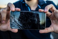 A smartphone with a cracked screen. Men`s hands hold a smartphone with a cracked screen royalty free stock image