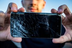 A smartphone with a cracked screen. Men`s hands hold a smartphone with a cracked screen stock photos