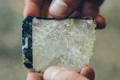 Men`s hands are holding cracked glass from a smartphone close-up on a blurred background. broken protection on the phone screen i. N macro copy space royalty free stock image