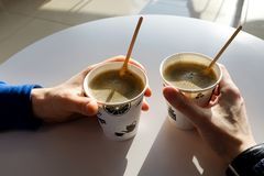 Men`s hands holding paper disposable cups of coffee on the table in the cafe. Breakfast stock photo