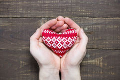 Men`s hands holding red knitted heart Stock Photos