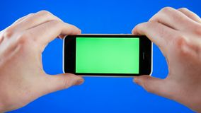 Men`s hands holding the smartphone in a horizontal position. Green screen on the phone and blue chromakey. No gesturing. No gesturing. Men`s hands holding the royalty free stock photo