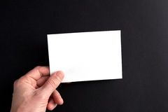 Men's hands holding a white blank sheet of paper Stock Image