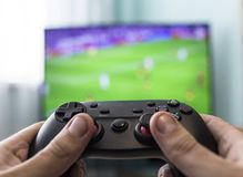 Men`s hands with a joystick on the background of a TV, playing football, close-up stock images