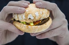 Men& x27;s hands keep a fresh juicy burger with tomato stock image
