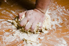 Men's hands knead the dough on the wooden table. The chef prepares the dough for Italian cuisine Royalty Free Stock Photo