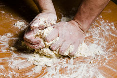 Men's hands knead the dough on the wooden table. The chef prepares the dough for Italian cuisine Stock Image