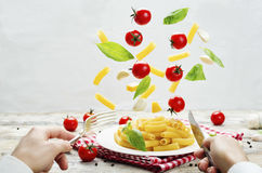 Men`s hands with knife and fork and a flying pasta with tomato a Stock Images