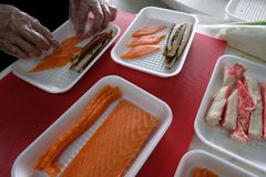 Men`s hands lay the ingredients for cooking for sushi and rolls. Fillet of salmon, smoked eel, crab meat in white rectangular pla stock photos