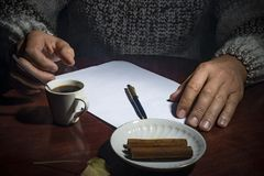 Men`s hands lie on the table, with a cup of coffee and a white sheet of paper, on a dark background Stock Images