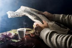 Men`s hands lie on the table, with a cup of coffee and a white sheet of paper, on a dark background Royalty Free Stock Image