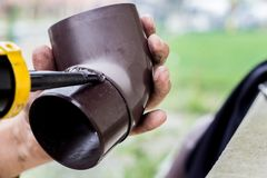 Free Men`s Hands Lubricate The Gutter With A Sealing Agent Stock Photo - 125404210