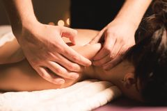 Free Men`s Hands Make A Therapeutic Neck Massage For A Girl Lying On A Massage Couch In A Massage Spa With Dark Lighting Stock Images - 128009694