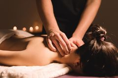 Free Men`s Hands Make A Therapeutic Neck Massage For A Girl Lying On A Massage Couch In A Massage Spa With Dark Lighting Stock Photo - 128517020