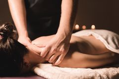 Men`s hands make a therapeutic neck massage for a girl lying on a massage couch in a massage spa with dark lighting. Close-up. Dark Key stock photos