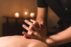 Men`s hands make a therapeutic neck massage for a girl lying on a massage couch in a massage spa with dark lighting. Close-up. Dark Key royalty free stock images