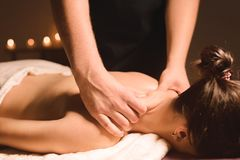 Men`s hands make a therapeutic neck massage for a girl lying on a massage couch in a massage spa with dark lighting. Close-up. Dark Key royalty free stock image