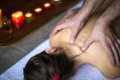 Men`s hands make a therapeutic neck massage for a girl lying on a massage couch in a massage spa with dark lighting. Healthcare, spa, and relax concept royalty free stock photo