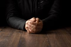 Men`s hands in prayer on a black background. The concept of faith, prayer, mourning, forgiveness, confession. Men`s hands in prayer on a black background The royalty free stock image