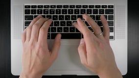 Men`s hands print on laptop, top view stock video