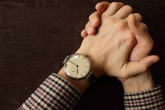 Men`s hands with retro wristwatch at the table. Meeting and deadline concept. Clasped hands. Elegant businessman hand top view. Stock Photos