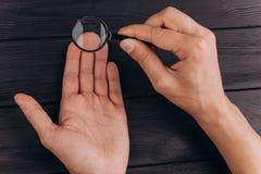 Men`s hands on a rustic black desk holding a magnifying glass. fingerprint examination. palm closeup stock images
