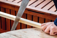 Men`s hands sawing a wooden bar with a hacksaw stock photo