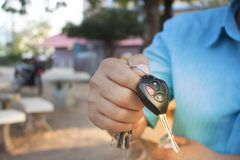 Men`s hands are showing car keys with unlocking symbols and alarms. Advancement in the car industry that uses remote control systems to facilitate customers royalty free stock photos