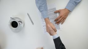 Men`s hands signing a document. Men`s hands working in an office and signing a document. The men are verifying data. Shaking hands. View from the top. Close-up stock video footage