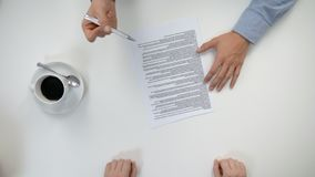 Men`s hands signing a document. Men`s hands working in an office and signing a document. The men are verifying data. Shaking hands. View from the top. Close-up stock footage