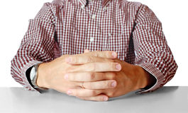 Men's hands sitting opposite at the table Stock Photos