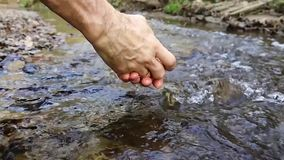 Men`s hands splashing in the stream.