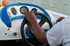 Men`s hands on the steering wheel of a motor boat stock photo