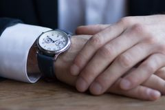 Men`s hands in a suit with white cuffs and watches on the arm royalty free stock photography