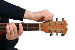 Men`s hands that tunes a six-stringed guitar. Isolated. Men`s hands in a black sweater that tunes the sound of a six-stringed guitar. Isolated on white Royalty Free Stock Photos