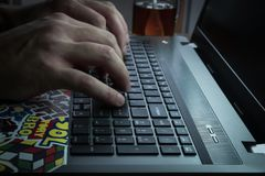 Men`s hands are typing on the laptop`s keyboard Stock Photos