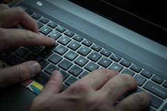 Men`s hands are typing on the laptop`s keyboard Royalty Free Stock Photo